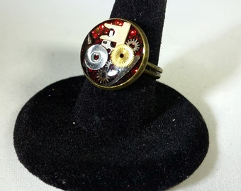 Round Steampunk Ring, Watch Gears & Parts in resin on a red background SR01