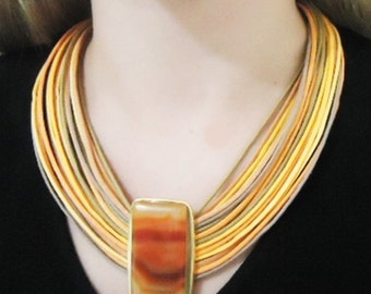 Necklace in fiber with agate stone, gold plated metal.