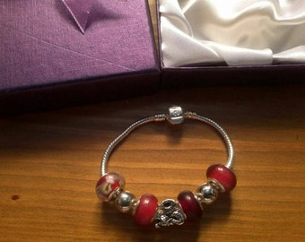 Stunning Reds with Dragon charm bracelet. Snake Chain with snap closure. Gift boxed.