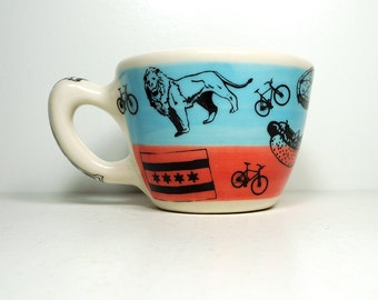 12oz cup/mug with Chicago city icons, on a colour block of sky blue and red-orange, ready to ship.