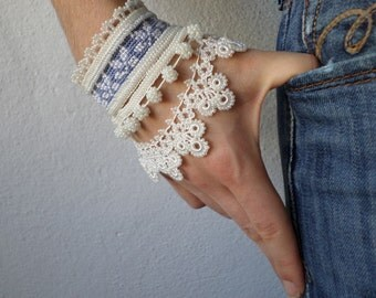 beaded crochet bracelet with white and blue-gray embroidered base and white seed bead decorations