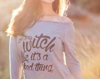 You Say Witch Like It's a Bad Thing. Off the Shoulder Long Sleeved Heathered Tee, Sport Striped Wrists.  Made in the USA.  Halloween Shirt