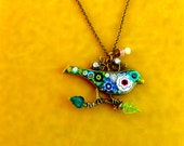 Bird Jewelry Pendant Fantasy Light Color Bird with Dangle. Millefiori Flowers in white blue, green yellow. Gold Colored Metal. Green leaves