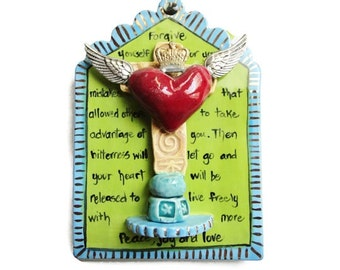 Forgiveness plaque with crowned heart and wings on a Cross