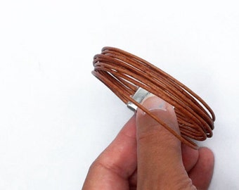 leather bracelet. single wrap bangle bracelet in camel brown. lobster clasp with chain and heart drop charm.