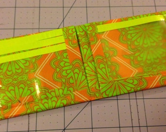 Green and orange duct tape wallet .