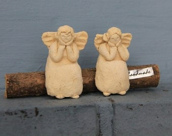Two small ceramic Angels sitting on a log