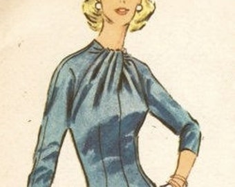 1950s pencil dress sewing pattern that has a striking draped crossed neck and detachable back panel. With either short or long sleeves.