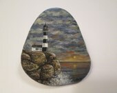 Lighthouse hand painted on a rock by Ann Kelly