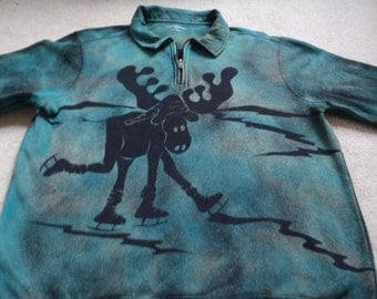 Man's medium jacket with a 3/4 zipper, cuffed sleeves, moose ice skating with a stocking cap, silhouette style, discharged & dye outer wear