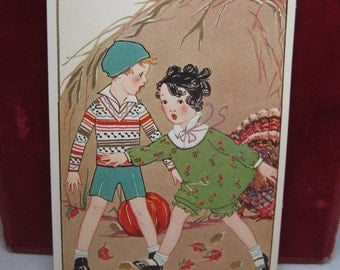 Adorable 1920's unused gold gilded embossed Thanksgiving postcard girl and boy run from a turkey big haystack pumpkin fall leaves