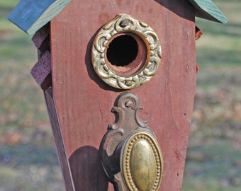 Red Birdhouse with Ornate Brass Door Hardware Perch and Green Wood Slat Roof and Brass Ringed Entry
