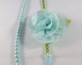 A Blue Sea Foam Floral Corsage With Green Olivine Crystals And Blue Pearls Choker Necklace