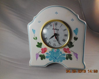 Beautiful white ceramic clock with blue and pink flowers.