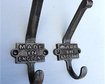 A pair of antique style Made in England cast iron double coat hooks