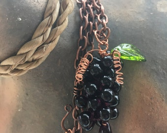 Grape cluster with leaf pendant on copper chain.