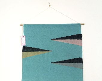 Triangle shapes wall hanging woven with pink, gray, and gold on a blue background