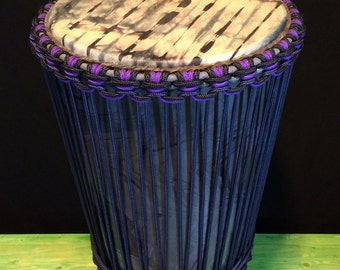 Large Ashiko drum that is swirl painted purple, black, and silver.  The natural goat skin is tie dyed.