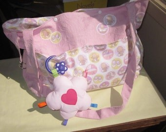 All about baby girls. Diaper bag, pad and bib included. This makes a great gift.