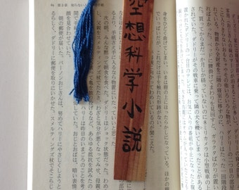 Science Fiction in Japanese calligraphy on a wooden bookmark with a sky blue tassel
