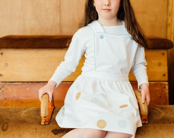 Pinafore Girls Dress- White. Children's dress Handmade in Britain. With Gold Glitter and printed blue spots. Retro style kids clothing