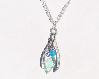"Silvertone and aqua  ""wishbone"" necklace made with ""It's a Mad, Mad, Mad, Mad World"" car glass."
