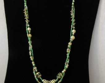 Necklace with Green and Gold beads with a green leaf pendant and a gold butterfly at the center of Necklace