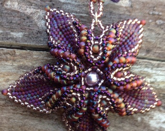 Beaded flower pendant in mixed purples and mauve on purple silk ribbon