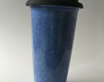 Blue ceramic travel mug hand decorated with white leaf design