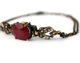 Vintage Bronze Bracelet with dark red crystal and small white crystals.