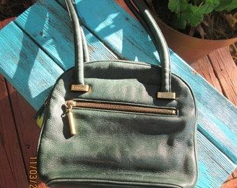 Vintage small dark green leather Etienne Aigner shoulder purse.  Metal zippers long rolled leather straps.Unique vintage purse.