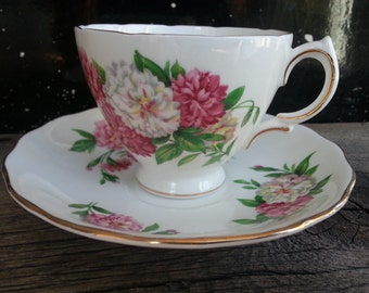 Vintage Royal Vale footed tea cup and saucer with pink and white mums on a white background - marked E8 on both pieces