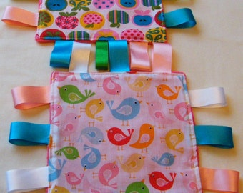 Set of 2 mini Taggy blankets, multi-coloured birds and apples.  2 co-ordinating mini Taggies in polycotton with fuchsia colour Minky fabric