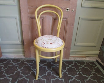 A yellow painted bentwood dining chair