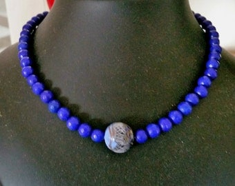 A beautiful royal blue jade necklace with a munro glass bead in centre