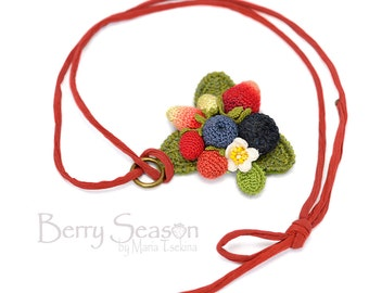 Crochet berry pendant on a red cord