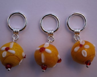 A set of three snagless yellow and red beaded Stitch markers for knitting. For needles up to 6mm. US size 10.