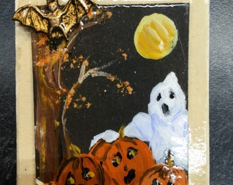 A Brooch with a moon,ghost,pumpkins, brass bat,all handpainted on a 2in x 1.75 matboard pin