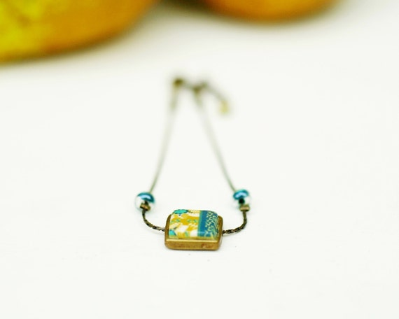 Minimalist bracelet 'Helixine' with yellow and dark turquoise flower patterns on a brass square and as erpentine chain