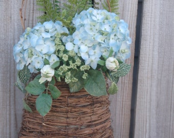 Blue hydrangea, willow hoops, white buds, green wildflower and mixed leaves