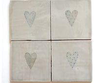 Set of four ceramic coasters with hearts. Taupe
