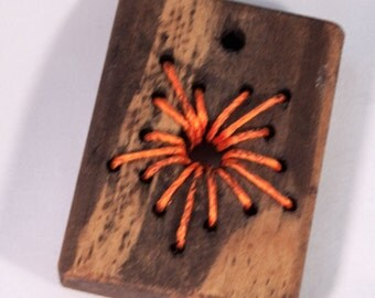 Thread flower on stained wood