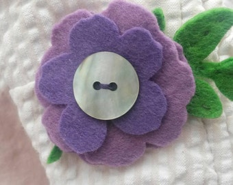 Purple felt flower brooch with vintage mother of pearl button.