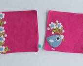 Set of two fuchsia pink wool fabric coasters with needle felted flowers and blue birdie bird