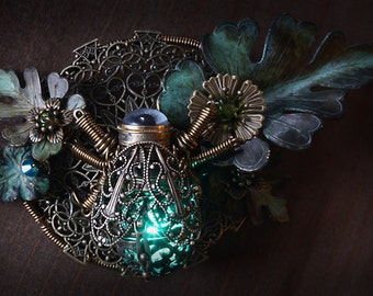 Glowing Steampunk Firefly Brooch made with antique clock parts and taxidermy glass eye