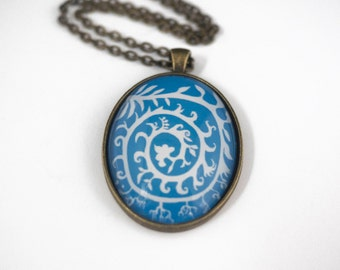 Abstract Botanical Spiral Pendant, Large Vintage Style Brass Oval Pendant with Illustration by June Hunter, White on Blue Background