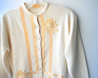 Mod vintage 60s off white orlon sweater -cardigan with a beige ribbon and two large flowers aplique. Sax Fifth Avenue. Size Small.