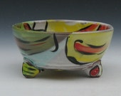 little bowl with red stripes  on yellow green and white with feet