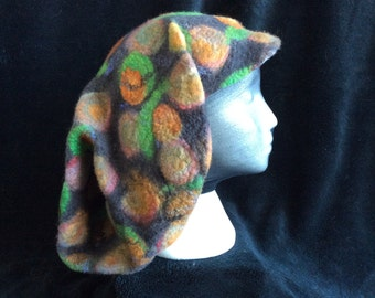 Uniquely designed wet felted ear flap hat with a bill, green, black,rust, spotted pattern