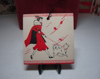 Colorful art deco unused 1930's unused bridge tally card stylish lady dressed in matching red dress and cape, hat waling spitz dog, windy